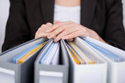 Midsection of businesswoman with binders at office-1