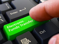 One Finger Presses Green Button Electronic Funds Transfer on Black Computer Keyboard. Closeup View. Selective Focus.